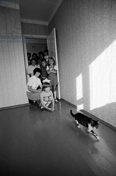 Evacuees from the Chernobyl nuclear reactor area let the cat first into the new house, 1986 (photo)