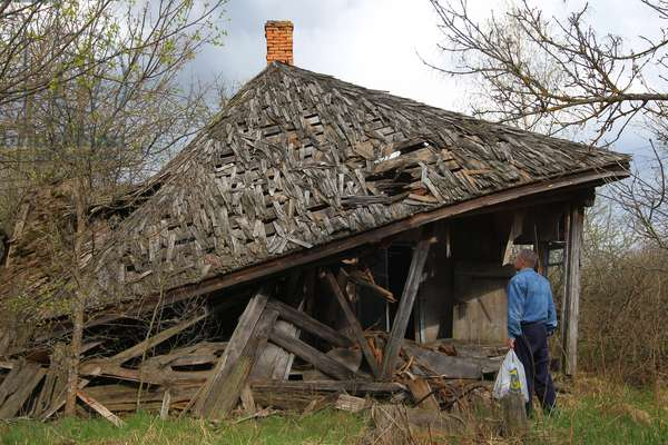 Nikolai Zkovorodin looks at his collapsed house in the village of Vezhishche, the Gomel region, that was evacuated in 1986 following the Chernobyl nuclear power plant disaster, 2012 (photo)