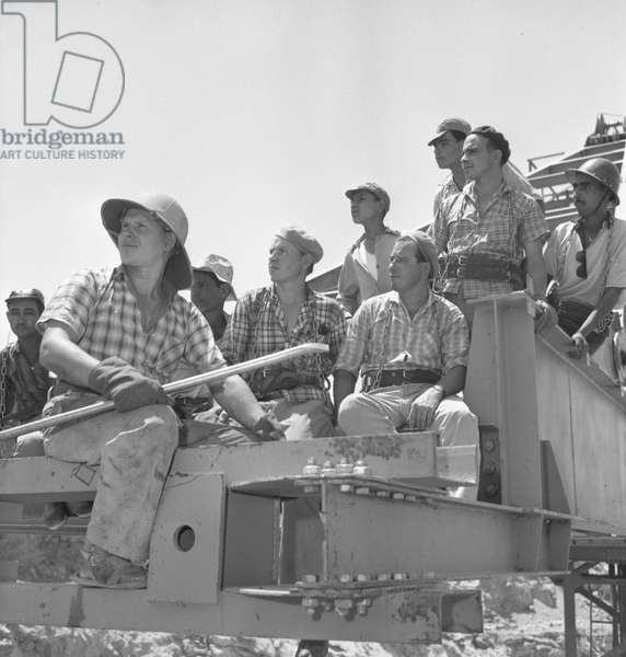 Building the Aswan Dam with Soviet technical assistance: Egyptian and Soviet assembly workers are preparing to span the Nile River, 1964 (b/w photo)