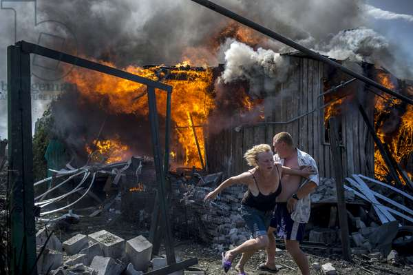 Local residents escape from a fire in the house destroyed in the Ukrainian armed forces' air attack on the village of Luganskaya, Valeriy Melnikov/Sputnik (photo)