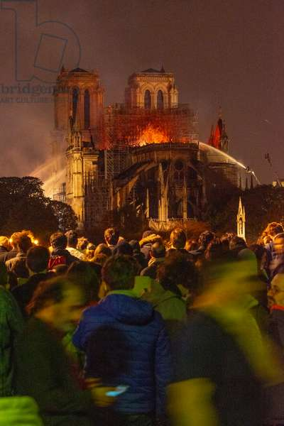 15.04.2019 People watch as firefighters douse flames from the burning Notre Dame Cathedral in Paris, France (photo)