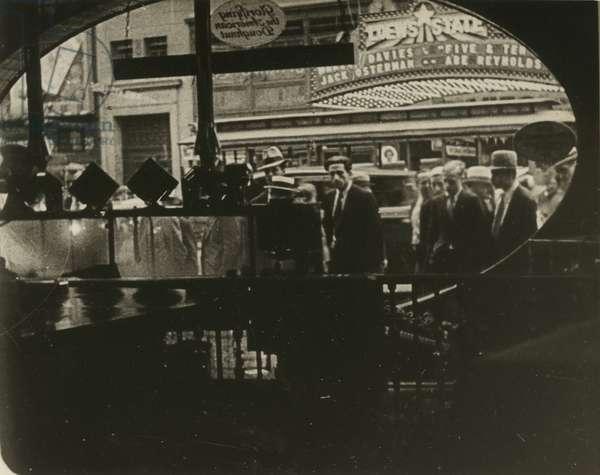 Pedestrians from inside a doughnut shop, Loew's State Theatre across the street, New York, USA, c.1920-38 (gelatin silver photo)