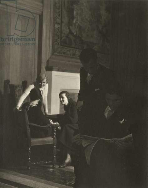 Two men reading a newspaper, three women in background, on board the Queen of Bermuda, Furness Bermuda Line, 1932, USA, 1932 (gelatin silver photo)