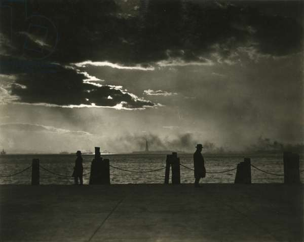 Figures silhouetted against sunset sky with Statue of Liberty in the background, Battery Park, New York, USA, c.1920-38 (gelatin silver photo)