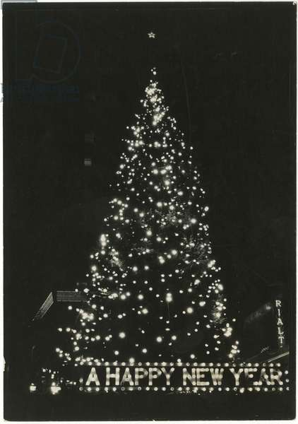 """Lit up Christmas tree with """"A Happy New Year"""" in lights at base, Times Square, Rialto Theatre in background, New York, USA, c.1920-38 (gelatin silver photo)"""