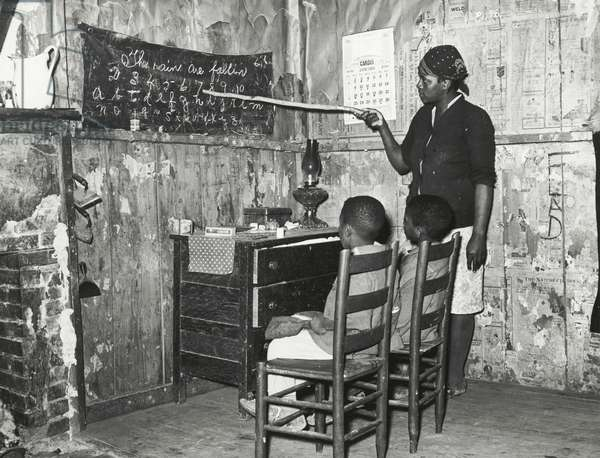 Negro mother teaching children numbers and alphabet in the home of a sharecropper, Transylvania, Louisiana, 1939 (b/w photo)