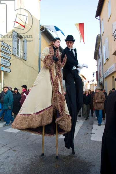 A couple on stilts, woman in long coat and man in tails and top hat,