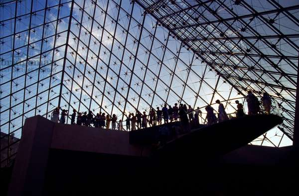 Viewing platform and people silhouetted agains the glass of the Louvre pyramid, Paris, France (photo).