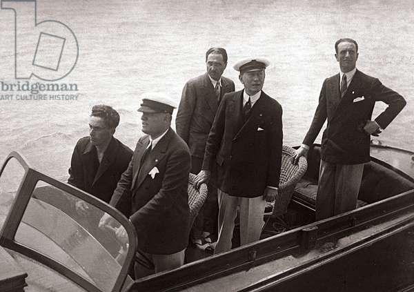 Mussolini et Marconi à Ostie (Ostia), le 9 juin 1930: Mussolini pilotant un canot à moteur et se dirigeant vers le bateau de Marconi, à l'extrème droite, le sous secrétaire du président Francesco Giunta - photographie n. b.