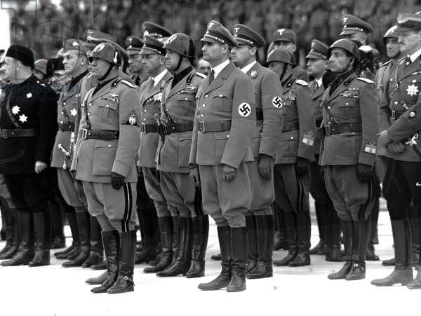 Rome, le 28/10/1937. Benito Mussolini, le general Viktor Lutze (a sa droite), commandant de la SA allemande, Augusto Antonelli, Gian Galeazzo Ciano (Ministre des affaires Etrangères), Rudolf Heff (Lieutenant de Hitler), Hans Frank (Ministre de la Justice du Reich), Achille Starace (Secrétaire du PNF), Alessandro Lessona ( sous-secretaire Colonie) et Ulrich Von Hassell (Ambassade allemand à Rome) pendant la celebration du 15eme anniversaire de la Revolution Fasciste.