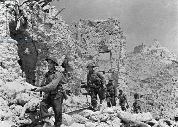 Cassino (Cassin), le 18/05/1944. La longue bataille de Cassino. Les soldats britanniques du Durham light entrent dans Cassino et passent à côté des ruines de l'Hotel delle Rose.