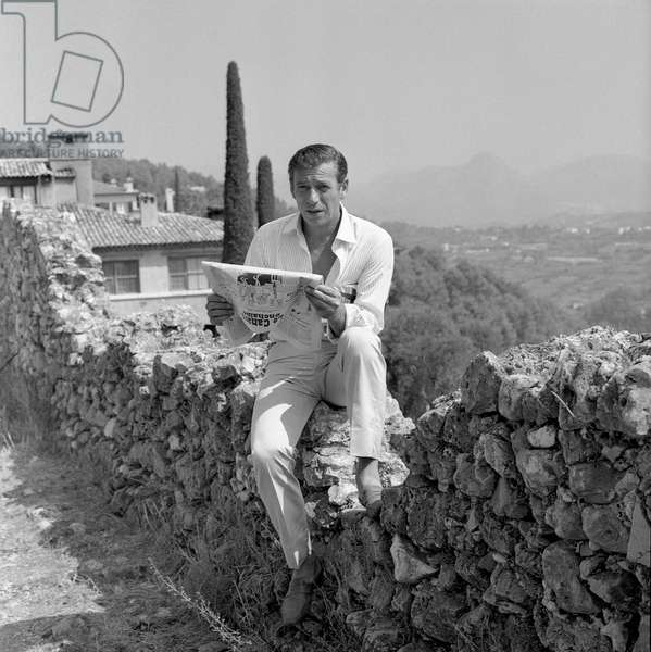 Saint-Paul-de-Vence 01/08/1964 Le comedien et chanteur Yves Montand lisant Le canard enchaine en vacances (Yves Montand during his holiday in Saint Paul de Vence (1964) Photographie