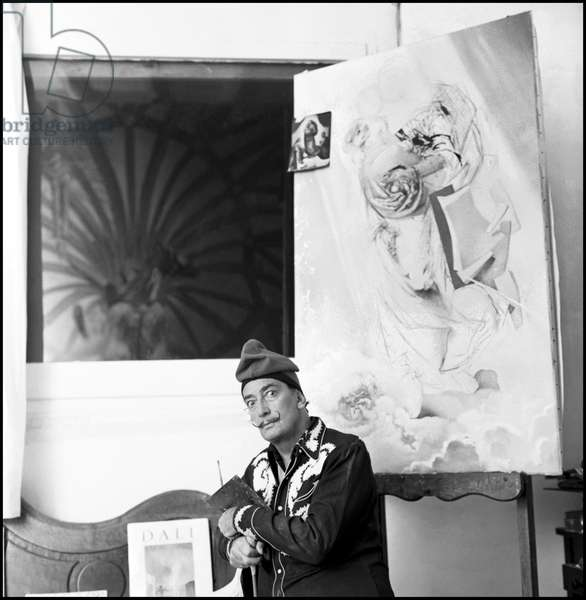 Portrait of Salvador Dali at home, surrounded by his works, Port Lligat (Spain), Nov 1957 (b/w photo)