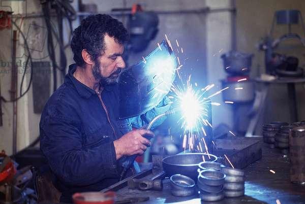 Lombardie. Un soudeur dans une usine fabriquant les extincteurs.