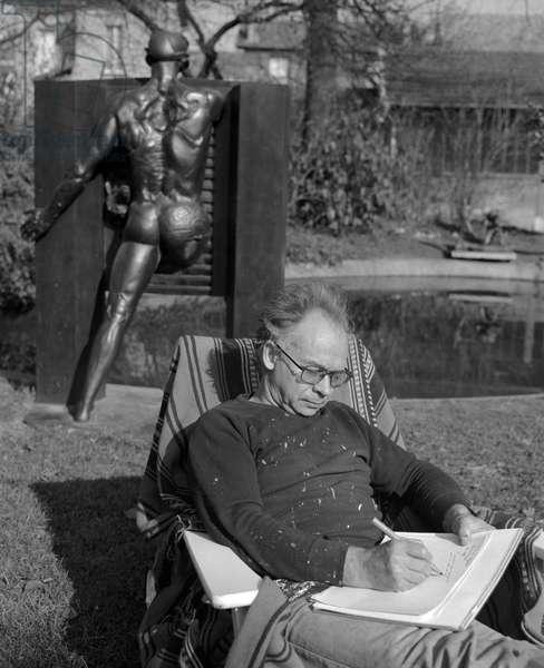 Portrait of Ipousteguy (born Jean Robert Ipousteguy) in front of his bronze sculpture L'Homme passant la Porte, dating 1966, 1976 (b/w photo)