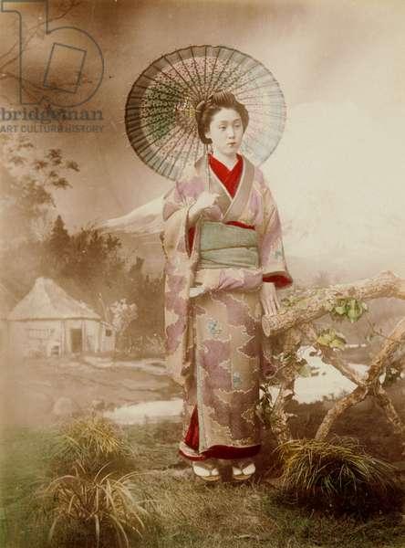 Woman in Photo Studio Against Backdrop Holding Umbrella, 1885-1900