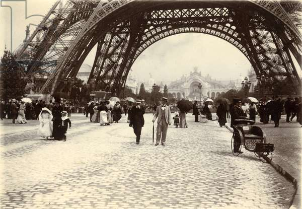 France, Ile-de-France, Paris (75): universal exhibition, Palais de l'Electricite seen through the arch formed by the feet of the Eiffel Tower - in the foreground, one of the 450 wheelchairs (wheelchairs) offered to visitors for a fatigue-free visit of the exhibition, field of March, 23 April 1900 (photo)
