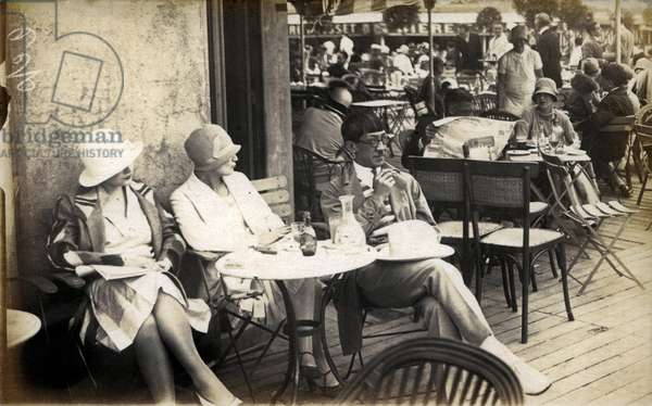 The Paris of the artists at the beautiful time: the painter Tsuguharu-Leonard Foujita (Tsugouharu Fujita 1886-1968) attached to the terrace of a Parisian cafe (perhaps in Montparnasse), in the company of two women who could be, one the muse and mistress and then wife of the painter Lucie Badoul (known as Youki), the other Kiki de Montparnasse (Alice Ernestine Prin, 1901- 1953), period anonymous photo card (b/w photo) -