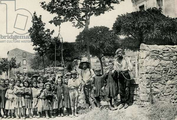 Village scene in Villeneuve des Corbieres (Aude, 11). Two winegrowers, still carrying sprayers to treat the vine, came to pose for the photo with the children at the exit of the school. Cliche Michel Jordy, early 20th century. Patrice Cartier Collection.
