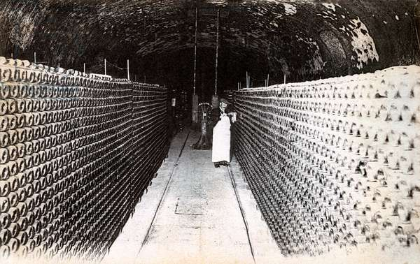 Bottles of champagne in a cellar, beginning of the twentieth century, Maison des Champagnes Veuve Clicquot (Clicquot-Ponsardin), Reims, France (b/w photo)