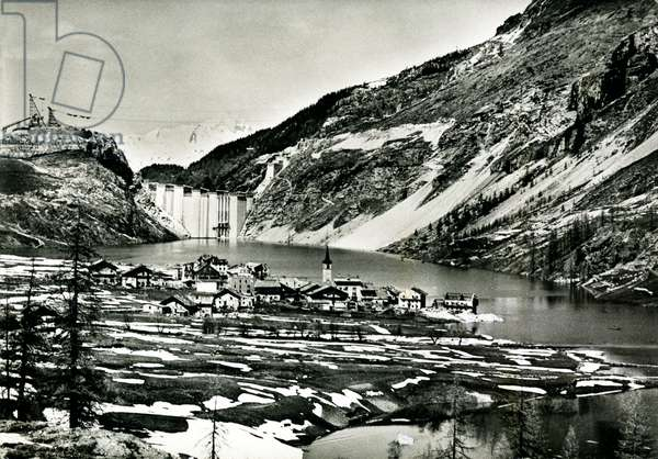 Dam of Tignes, with the village about to be engulfed by the artificial lake (postcard, circa 1952)