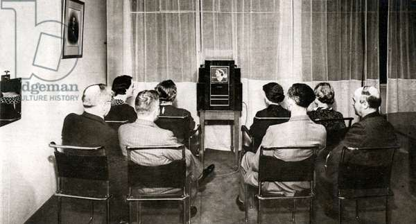 A group of people watching television in 1936. Promotional photo of Grammont, June 1936.