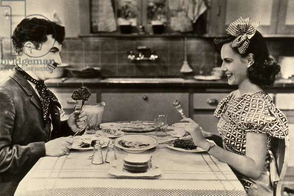 "Charlie Chaplin (1889-1977) and Paulette Goddard in the film ""The Modern Times"" (Modern Times, 1936). Charlot and ""the girl"" at the table."