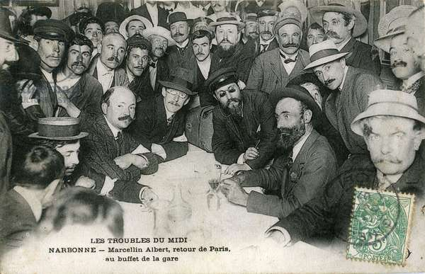 Revolt du Midi viticole: After an interview in Paris with the president of the board, Minister of Interior Georges Clemenceau, Marcelin (Marcellin) Albert, the apostre des vignerons, returns to his village of Argeliers. Here he is photograph (2nd sitting from the right) at the buffet of Narbonne station on June 24. Two days later, as a prisoner, he was imprisoned at Montpellier prison.