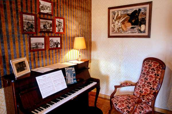 Narbonne (Aude, 11, Occitanie): interior salon of the home of singer Charles Trenet (1913-2001), transformed into a museum. Son piano et son armchair - House of the famous french singer Charles Trenet (museum, where he was born). Photo by Patrice Cartier -