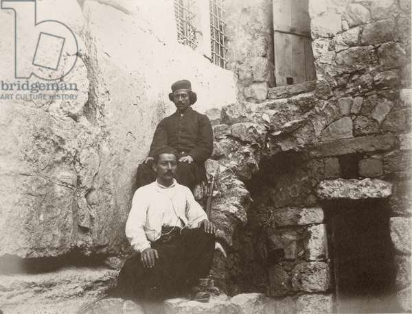 Two men sitting next to the lintel of Barclay's Gate in the Western Wall of Temple Mount, Jerusalem, 1866 (b/w photo)