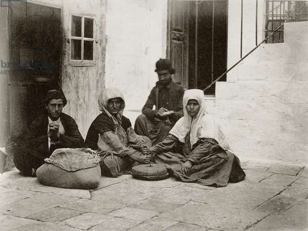 Women grinding flour with round millstones within a courtyard of a house in Jerusalem, 1867 (b/w photo)