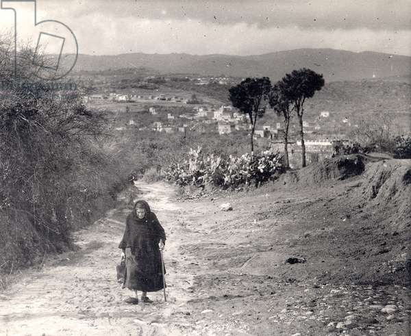 Old woman with a cane walking up a hill, c.1944-46 (b/w photo)
