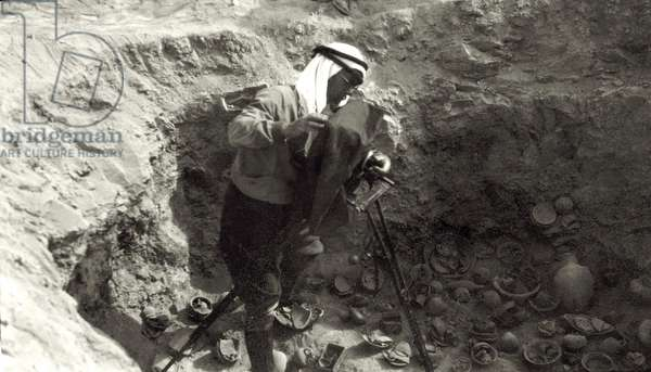 Professor John Garstang photographing broken pottery 'in situ' at the Jericho excavations, 1930-36 (b/w photo)