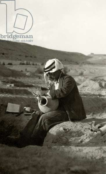 John Garstang at Jericho studying a Middle Bronze Age jug from c.1800 BC, 1930 (b/w photo)