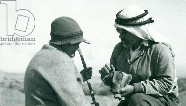 John Garstang showing a piece of 'Yahudieh Ware' pottery chalice to Mrs Garstang, 1930 (b/w photo)