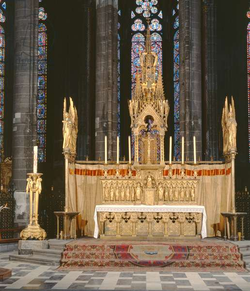 High Altar in neo-gothic style, surrounded by 4 angels carrying the instruments of the Passion of Christ with a tabernacle surmounted by an elaborately decorated spire (photo)