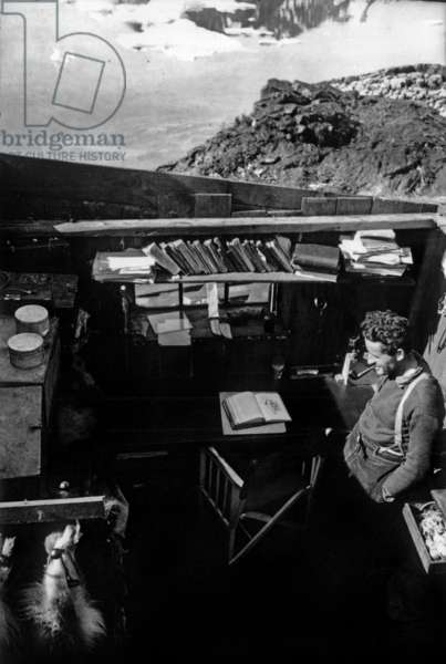 Paul-Emile Victor smoking pipe in his hut (during building) during his polar expedition in Greenland, Kangerdlugssuatsiak, Autumn, 1936 (b/w photo)