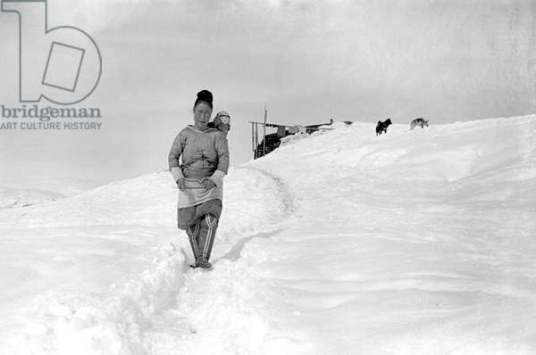"Inuit woman carrying her baby in her ""amaout"", Kangerdlugssuatsiak, Greenland, Winter, 1936-37 (b/w photo)"