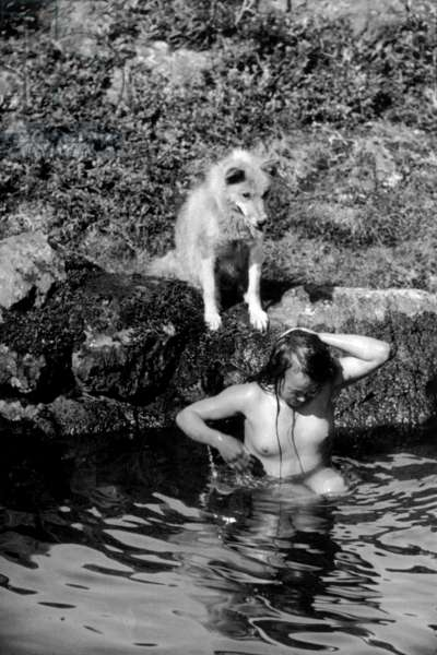Young inuit woman bathing in a lake, during polar expedition in Greenland, Kangerdlugssuatsiak, Autumn, 1936 (b/w photo)