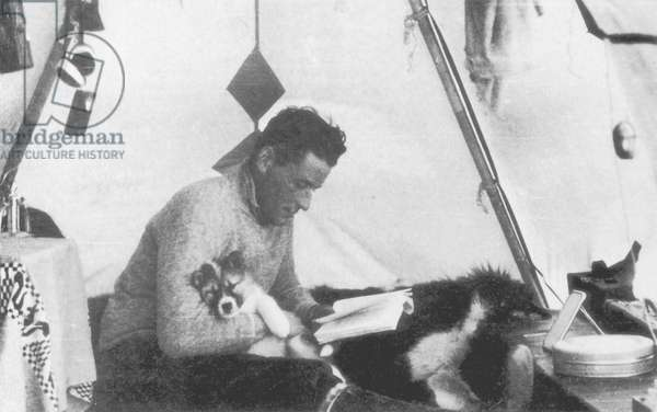 During the construction of the family common home, Paul-Emile Victor lived in a tent. Here he reads, a puppy in arms, Kangerlugsuatsiak, Greenland, August 1936 (b/w photo)