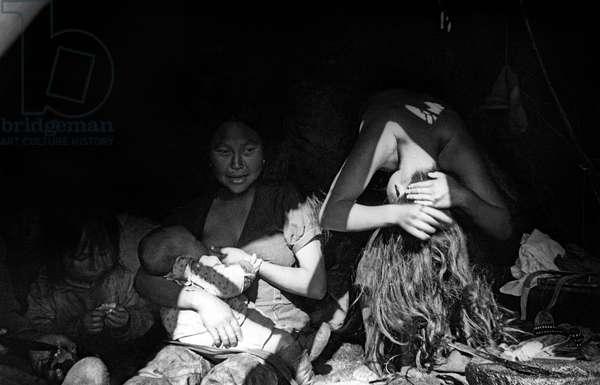 "Inuit woman, shared hut: on l: Paoda with her baby, on r young woman making her chignon (""pikiwa""), Kangerdlugssuatsiak, Greenland, Autumn, 1936 (b/w photo)"