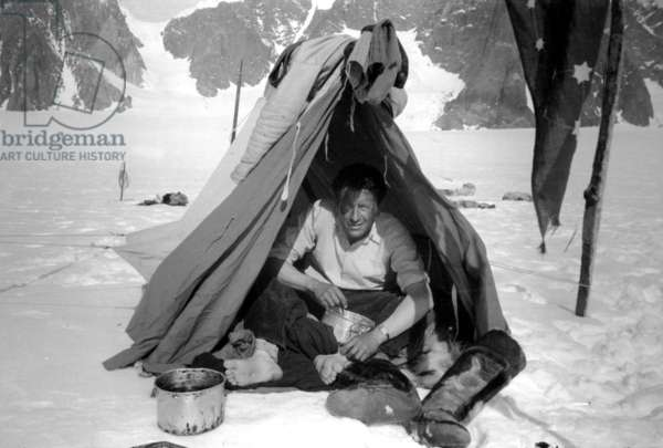 Paul Emile Victor having a meal at his camp at Mont Forel, Greenland, June, 1937. He's waering kamiks (eskimo boots made with seal skin): on r: pennant he made for his crossing if Greenland in May-June, 1936 (b/w photo)