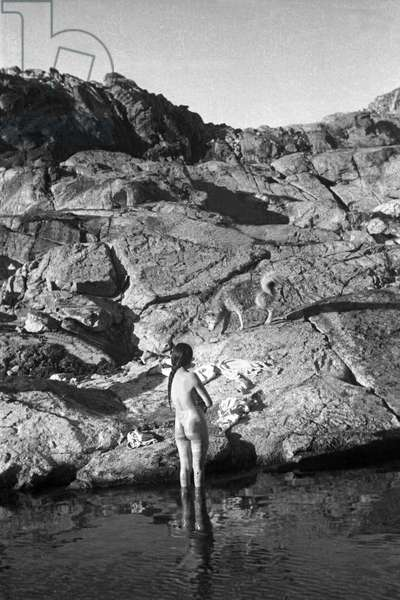 Doumidia, the Inuit companion of Paul Emile Victor, bathes in a lake in the Kangerdlugssuatsiak Fiord (east coast of Greenland) photo taken in the fall, 1936 by Paul-Emile Victor during his wintering, 1936-1937 (b/w photo)