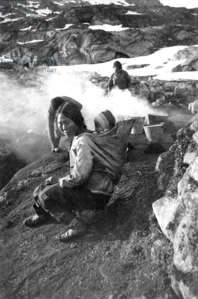 "Paoda carrying her baby in her ""amaout"", fjord of Kangerdlugssuatsiak, Summer, 1936 (b/w photo)"