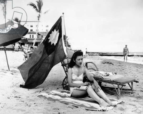 USA / China: Ruth Lee, an American woman of Chinese descent, displays the flag of the Republic of China while she sunbathes so that other beach-goers do not mistake her for a Japanese. Florida, 15 December 1941