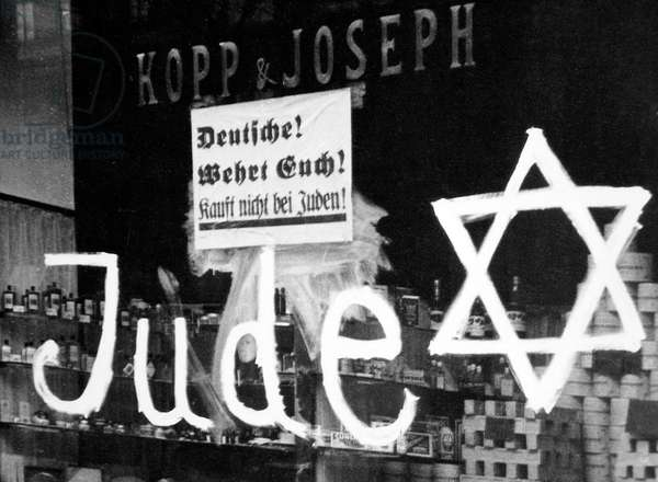 Germany: A Jewish-owned shop vandalized by Nazis with poster reading 'Germans Defend Yourselves - Don't Buy from Jews', 1938 (b/w photo)
