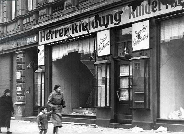 Germany: On the night of the 9-10 November 1938 the Nazis organised 'Kristallnacht', the night of the broken glass. This mother and child pass the remains of a Jewish owned shop the morning after Kristallnacht (b/w photo)
