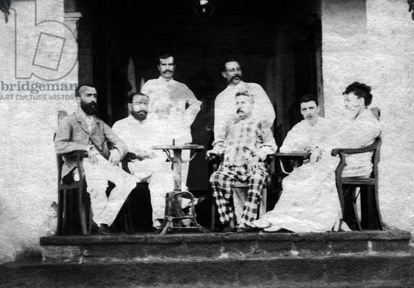 France/Yemen: Arthur Rimbaud (1854 - 1891, second from right) seated with unidentified Europeans on the terrace of the Hotel of the Universe, Aden, 1880