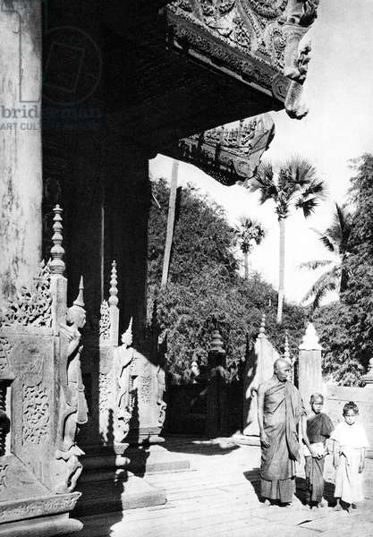 Burma/ Myanmar: A Buddhist monk and two young novices stand outside the Queen's Golden Monastery in Mandalay Palace, c.1920s.