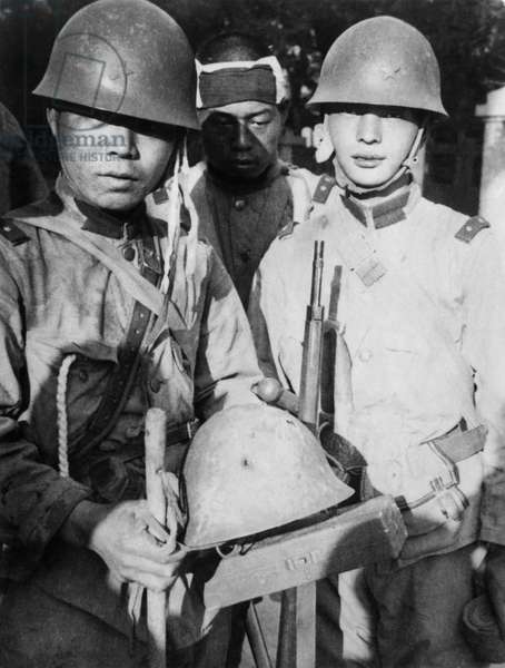 China / Japan: Imperial Japanese soldiers display a bullet-pocked helmet that saved the life of their comrade (centre) during the Battle of Beijing, Second Sino-Japanese War, July 1937 (photo)